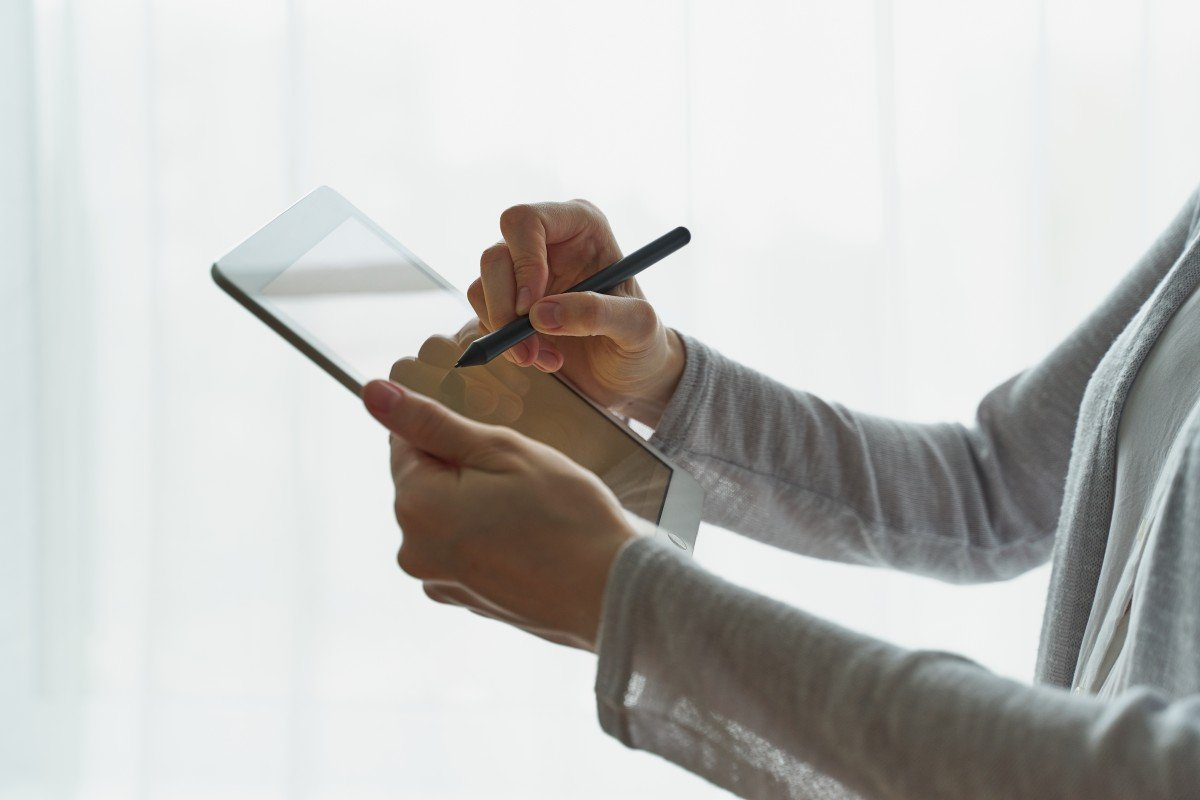 woman uses stylus to sign her name on tablet