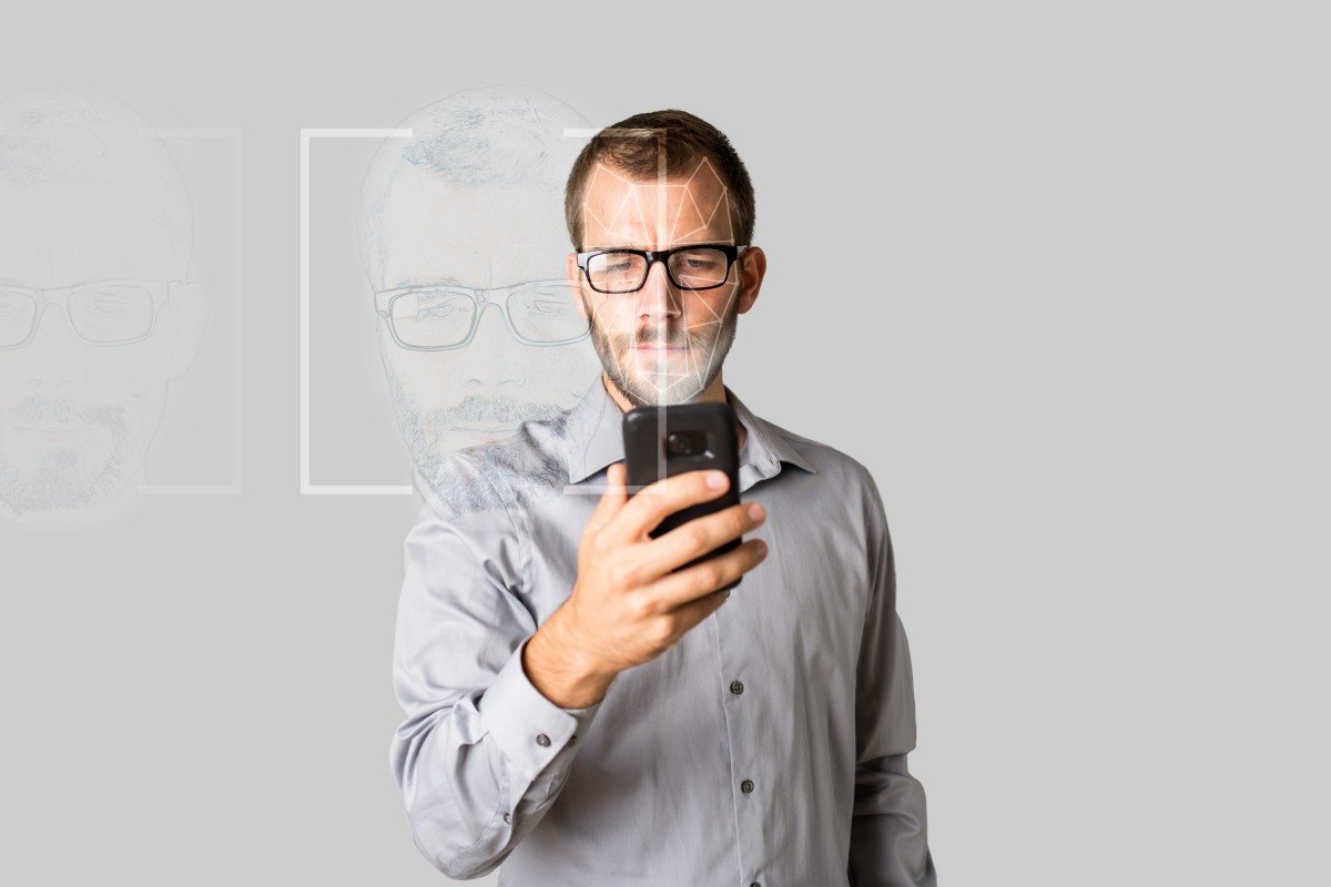 man in glasses holds phone while facial recognition scans his face