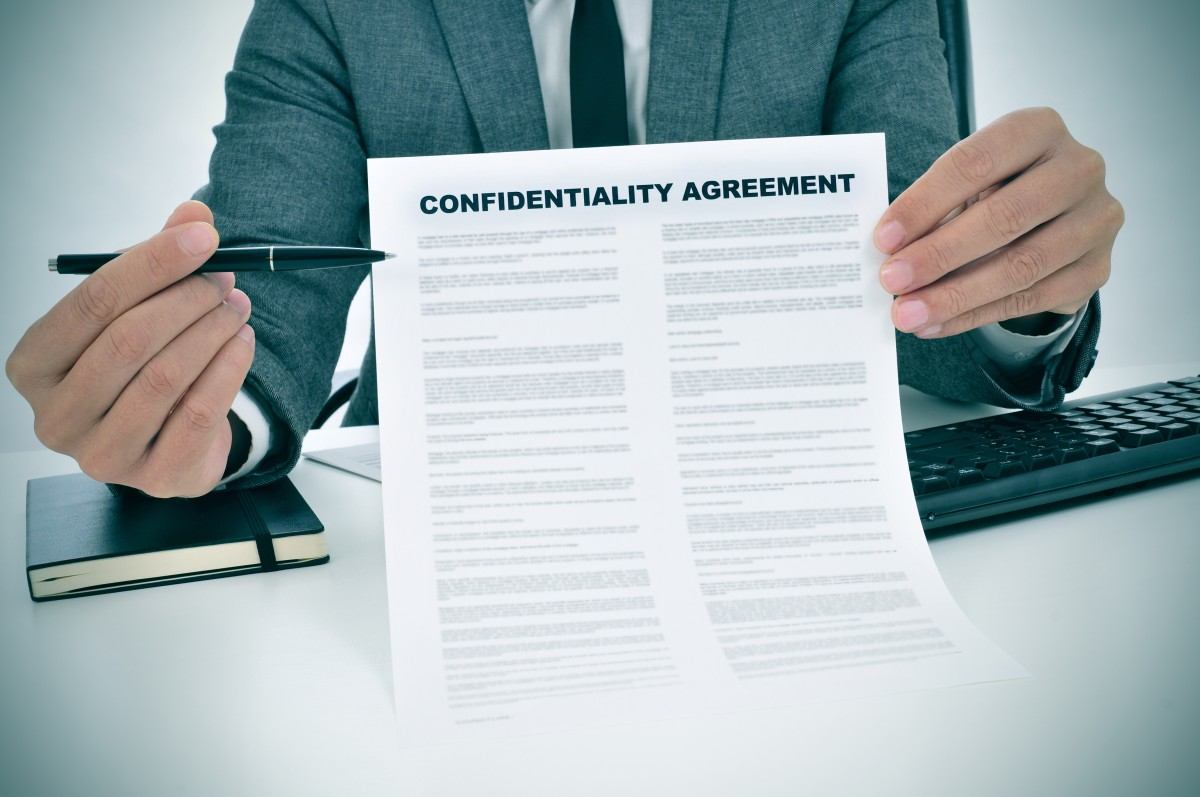 man in suit holds pen for signing of confidentiality agreement